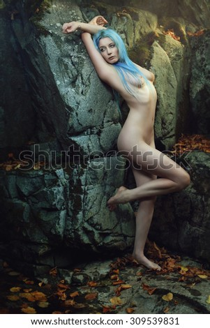 Beautiful ethereal maiden posing in dark cave. Myth and fairy tale - stock photo