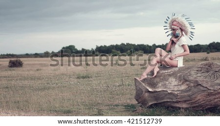 Beautiful ethnic lady with roach on her head on the field - stock photo
