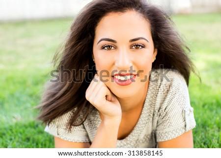 Beautiful ethnic woman sitting outside - stock photo