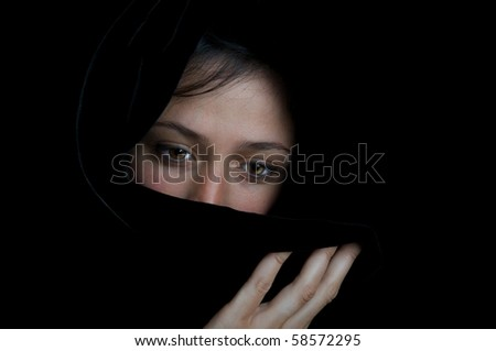 Beautiful ethnic woman with sad eyes, wrapped in a black scarf. - stock photo