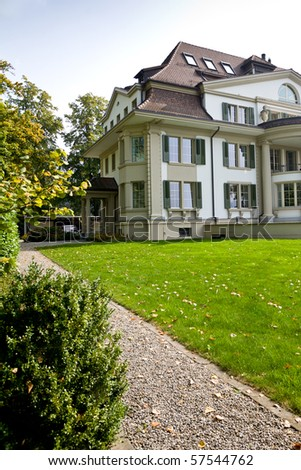 Beautiful european house with green lawn - stock photo