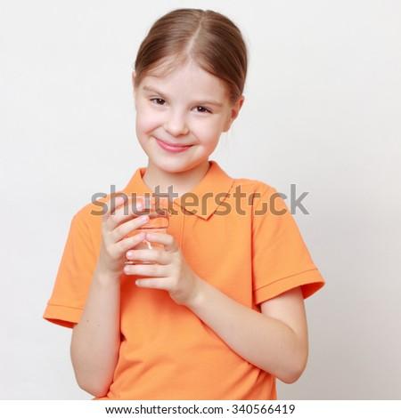 Beautiful european little girl holding cow milk in glass - stock photo