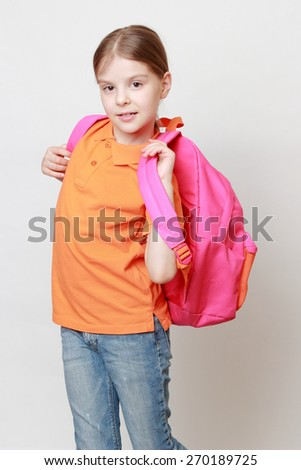 Beautiful european little girl holding school bag - stock photo