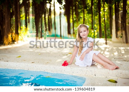 Beautiful european toddler girl sitting near turquoise swimming pool with exotic red flower