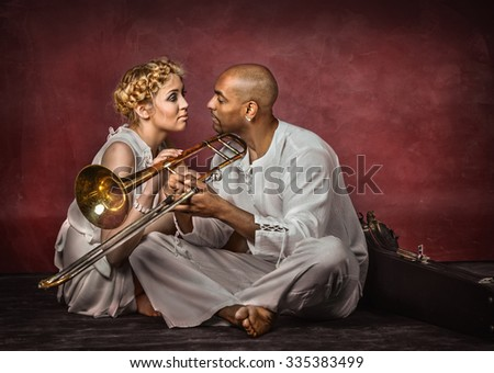 Beautiful european woman and attractive cuban trombone player on dark red background, studio shot - stock photo