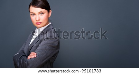 Beautiful European young solid businesswoman standing with hands folded against grey background - stock photo