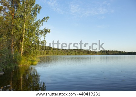 Beautiful evening by the lake during sunset. Some rocks are in the water. Birch leaves are glowing due to sun going down. Image taken in Finland. - stock photo