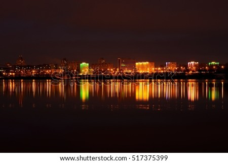 beautiful evening city landscape with reflection in the ice lake