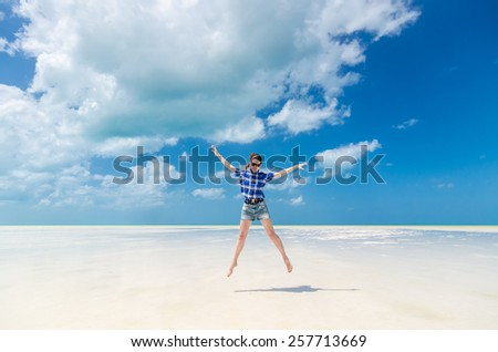 Beautiful excited cheerful young woman with arms out in blue cotton checked shirt and sunglasses jumping on the background of desert sea lagoon at white sandy beach in the Caribbean sea, Holbox,Mexico - stock photo