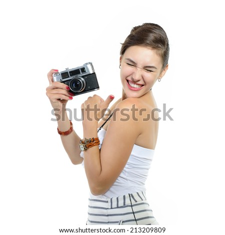 Beautiful excited girl takes picture with retro photo camera, over white. - stock photo