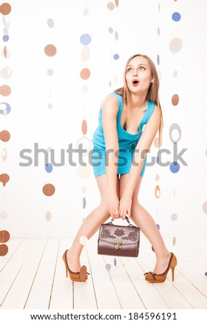 Beautiful excited woman  in blue dress holding handbag in studio - stock photo