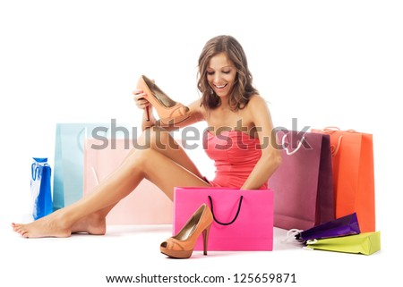 Beautiful excited woman with new shoes sitting among colorful shopping bags - stock photo