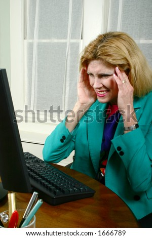Beautiful executive business woman gets a headache from working at a computer in the office.