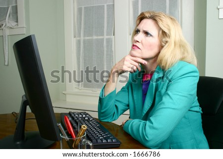 Beautiful executive business woman looking away from her computer to contemplate in the office. - stock photo