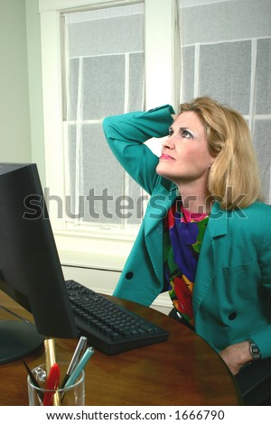 Beautiful executive business woman with a hand on her head thinking at a computer in the office. - stock photo