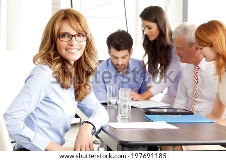 Beautiful executive businesswoman sitting at meeting.  Business group.  - stock photo