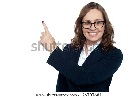 Beautiful executive in suit gesturing copy space, smiling warmly