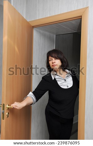 Beautiful executive woman opening the door in the office - stock photo
