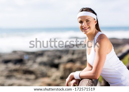 beautiful exercise woman outdoors on beach looking at the camera