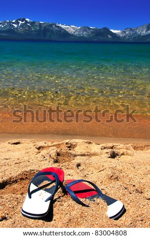 Beautiful exotic beach for relax with snow mountains azure clear water and flipflops on sand. Focus on Flip flops - stock photo