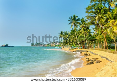 Beautiful exotic Caribbean beach of golden sand full of palm trees - stock photo