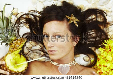 Beautiful exotic girl with Hawaiian accessories lying - stock photo