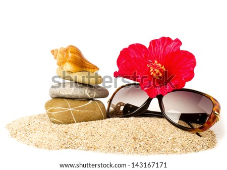Beautiful exotic shell, stones, red flower and glasses on sand - stock photo