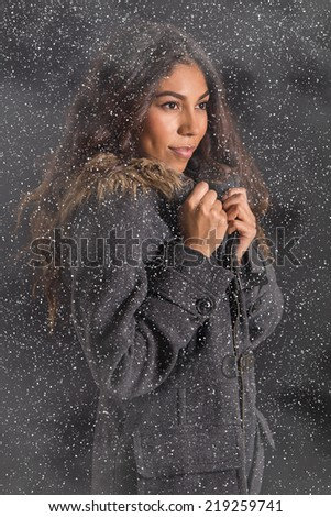 Beautiful exotic woman in snow storm - stock photo