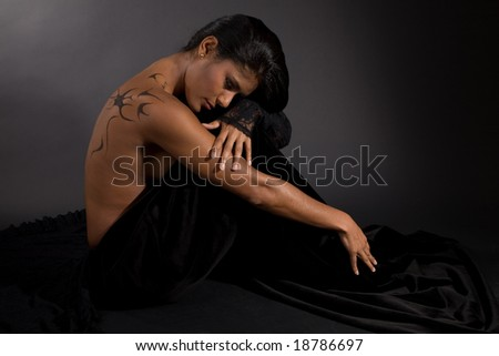 Beautiful exotic woman on black background looking down
