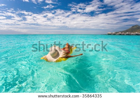 beautiful exotic woman with yellow inflatable raft in turquoise waters near tropical resort - stock photo