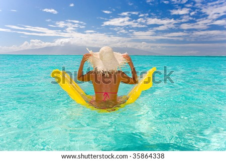 beautiful exotic woman with yellow raft in turquoise waters - stock photo