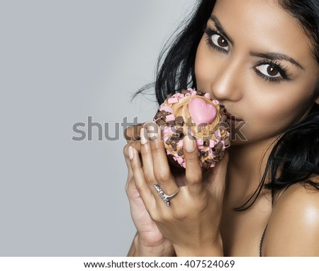Beautiful exotic young woman holding heart cupcake close to her face