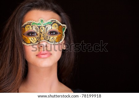 Beautiful exotic young woman wearing a masquerade mask against a black background.
