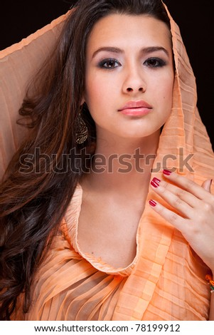 Beautiful exotic young woman wearing a veil against a black background. - stock photo