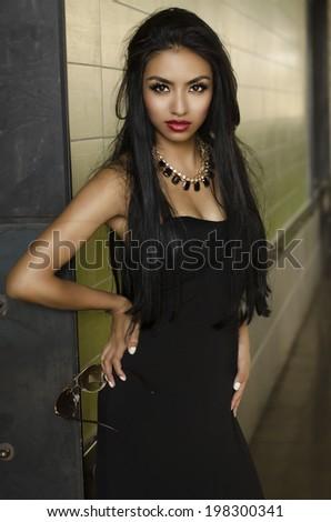 Beautiful exotic young woman wearing black dress - stock photo