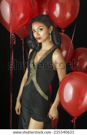 Beautiful exotic young woman wearing black dress with party balloon background  - stock photo