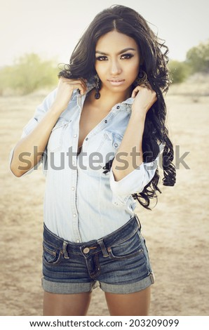 Beautiful exotic young woman wearing denim shorts and shirt in desert location - stock photo