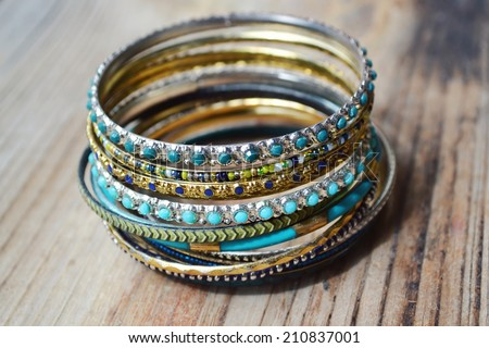 Beautiful expensive gold bracelets on wooden background - stock photo