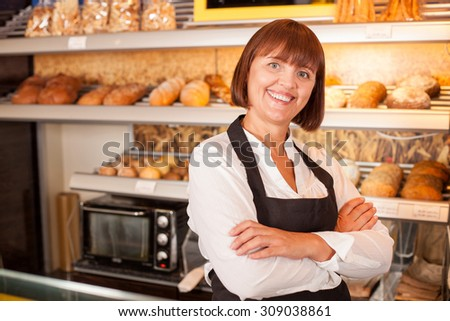 Beautiful experienced chef is standing near baked products and smiling. The woman is satisfied with her work. She crossed her hands. Copy space in left side - stock photo