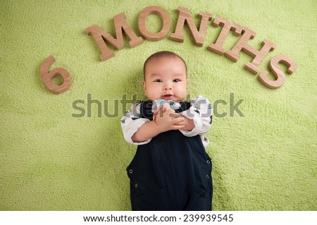 Beautiful expressive adorable happy cute laughing smiling asian baby infant face clapping hands. six months. Age concept. - stock photo