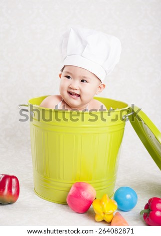 Beautiful expressive adorable happy cute laughing smiling baby infant face. .Baby wearing a chef hat with vegetables and pan. Use it for child, healthy food concept - stock photo