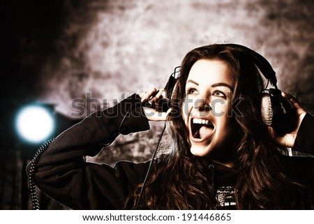 Beautiful expressive girl listening to music in headphones and singing. Grunge style. Disco, party. - stock photo