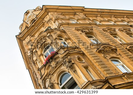 Beautiful facade of a historic building with statues, stucco molding, columns and red flowers - stock photo