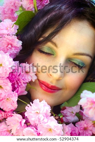 Beautiful face among pink flowers of cherry