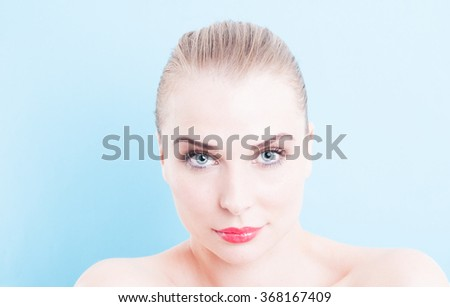 Beautiful face female model on blue or turquoise background as makeup and cosmetics concept