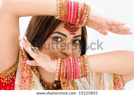 Beautiful face of a Bengali bride with her arms across her head covered with colorful bracelets, isolated - stock photo