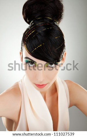 Beautiful face of a glamour woman with modern curly hairstyle and brightly makeup over gray background - stock photo