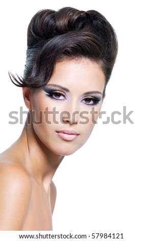 Beautiful face of a glamour woman with modern curly hairstyle and colored makeup
