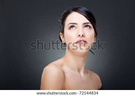 Beautiful face of a glamour woman with modern hairstyle and brightly makeup looking up - stock photo