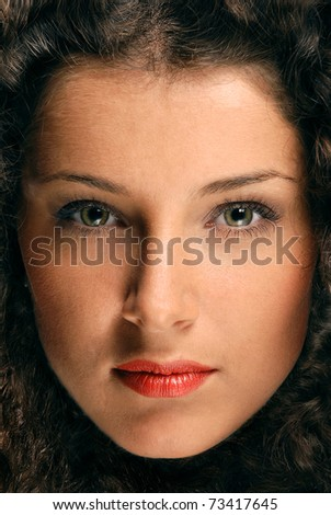 Beautiful face of a young brunette framed by curly hair
